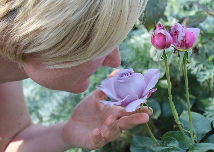 Mujer oliendo rosa