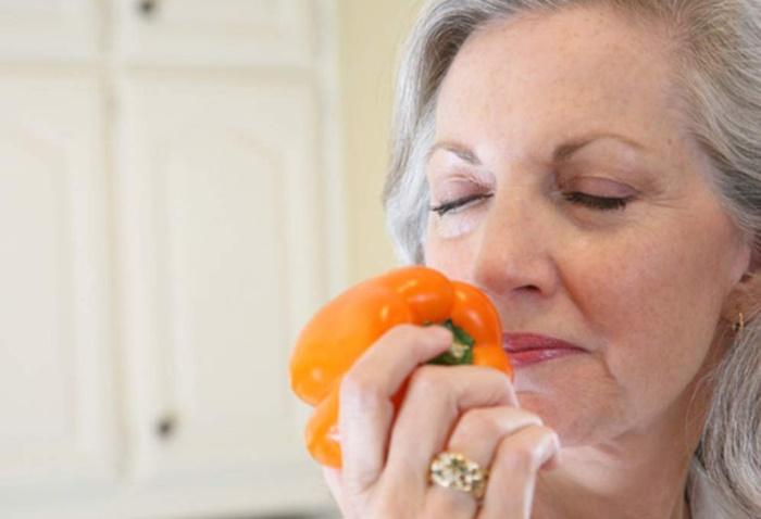 Señora oliendo pimiento