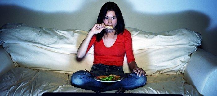 Chica cenando frente a TV