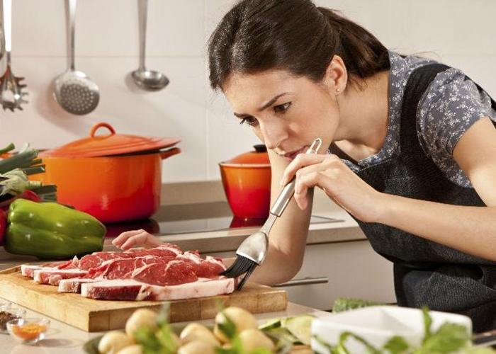 Mujer cocinando carne