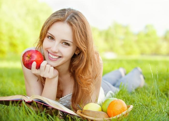 Chica comiendo frutas y leyendo