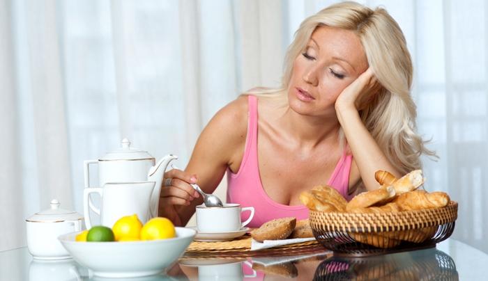 Mujer cansada en el desayuno